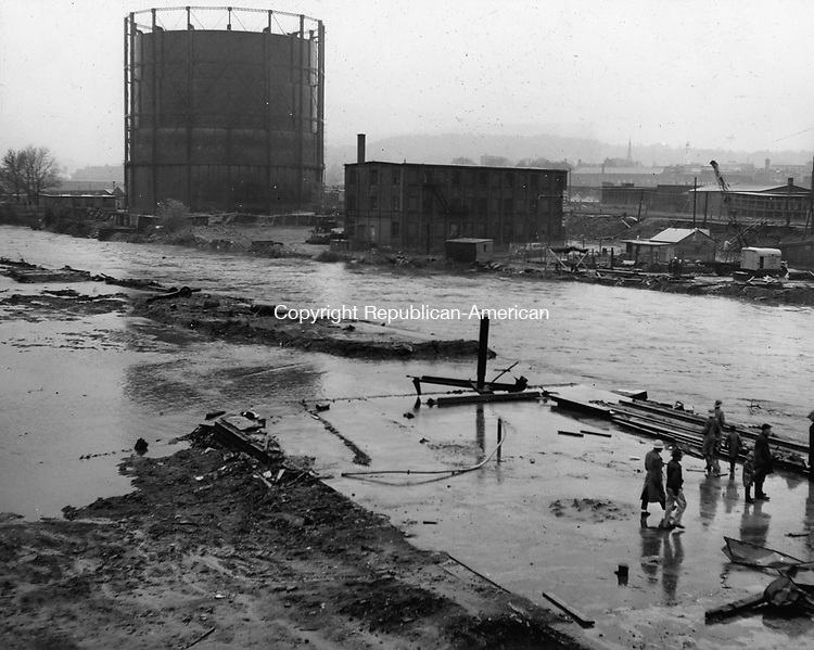 The gas works of the Connecticut Light and Power Co. across the river from South Main Street was once more virtually isolated by the rampaging Naugatuck. This scene was taken early Saturday morning before the river had reached its full flood stage.