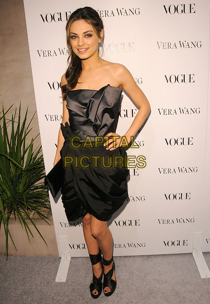 MILA KUNIS .at the Vogue Dinner honoring Vera Wang Celebration of Vera Wang on Melrose Opening in West Hollywood, California, USA, March 2nd 2010..full length grey gray strapless silk satin ruched dress black hand on hip sandals ankle tie tied clutch bag .CAP/RKE/DVS.©DVS/RockinExposures/Capital Pictures.