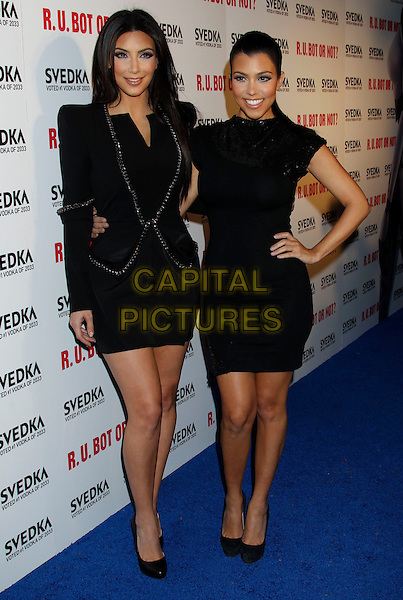 "KIM KARDASHIAN & KOURTNEY KARDASHIAN.""Battle Of The Bots"" Sponsored by Svedka Vodka at Wonderland,  Hollywood, California, USA, .22nd May 2010..full length black dress shoulder pads long sleeved sleeves hand on hip shoes smiling family sisters siblings  .CAP/ADM/MJ.©Michael Jade/AdMedia/Capital Pictures."