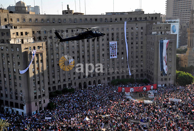 An Egyptian military helicopter flies over Tahrir Square as protesters take part in a protest in support of the army, Cairo, Egypt, 26 July 2013. Egyptian authorities on 26 July ordered ousted president Mohammed Morsi to be detained for 15 days pending further investigations on charges of conspiring to carry out 'hostile acts' in the country, reported state-run newspaper al-Ahram online. Morsi's backers and opponents were, meanwhile, rallying for rival demonstrations across the country, mainly in Cairo. Scores of anti-Islamist activists were turning out at central Cairo's Tahrir Square in response to a call made by army chief Abdel-Fattah al-Sisi, who engineered Morsi's ouster. Photo by Ahmed Asad