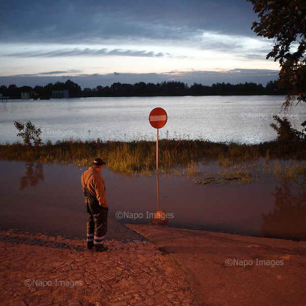 DOBRZYKOW, POLAND, MAY 24, 2010:.Villager on early morning, observing rising waters..The latest chapter of disastrous floods in Poland has been opened yesterday, May 23, 2010, after Vistula river broke its banks and flooded over 25 villages causing evacualtion of most inhabitants..Photo by Piotr Malecki / Napo Images..DOBRZYKOW, POLSKA, 24/05/2010:.MIeszkaniec obserwuje podnoszaca sie wode wczesnym rankiem . Najnowszy akt straszliwych tegorocznych powodzi zostal rozpoczety wczoraj gdy Wisla przerwala waly na wysokosci wsi Swiniary kolo Plocka..Fot: Piotr Malecki / Napo Images ..