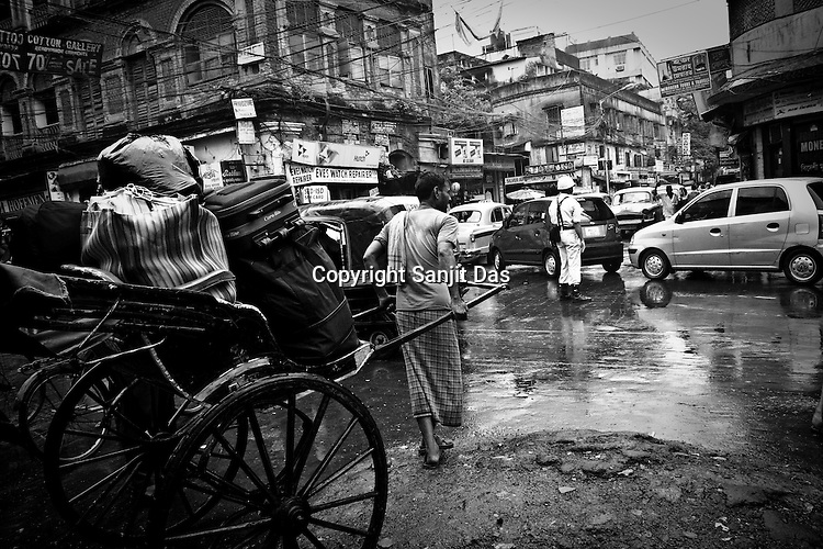 A rickshaw puller is seen taking a rickshaw full of luggage through the busy street during the monsoon rain in Calcutta, India. 93 out of every 100 rickshaw pullers are homeless. They sleep after the city sleeps and wake up before everyone else does. Many of them are the sole bread earners for their family. Many plus 40. Many minus any other specialisation for any other job. Of the twenty four thousand rickshaw pullers, only 387 have licenses. .Many rickshaw pullers earn a meagre wage of 100-150 rupees (US $ 2.25-3.5) a day of which they have to give a daily rickshaw rent of 60 (US$ 1.35) rupees to the agent at the end of the day.