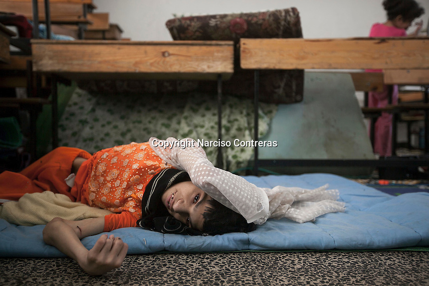 """In this Saturday, Aug. 16, 2014 photo, Nisma, a 22 yo youth who is mental disable, lies on a couch inside a classroom at the Al-Zaytoon UN School turned into a temporary refugee after her family fled from Shuyaja neighborhood when the IDF targeted and destroyed their house during the """"Protective Edge"""" military operation in Gaza Strip. (Photo/Narciso Contreras)"""