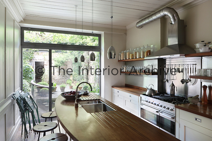 A modern kitchen with pendant lights hanging above an island unit. Glass storage jars are arranged on wooden shelves either side of a stainless steel range oven.