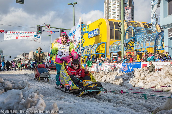 Monica Zappa and team leave the ceremonial start line with an Iditarider at 4th Avenue and D street in downtown Anchorage, Alaska during the 2015 Iditarod race. Photo by Jim Kohl/IditarodPhotos.com