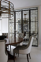 Reflected in iron framed mirror doors that conceal china and linens stored behind them, the custom made circular pedestal dining table and chairs continue a monochromatic scheme. The reflection creates a sense of space in the room.