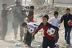 A soldier from Company D, 2nd Battalion, 7th Cavalry Regiment hands out soccer balls to a group of boys in Mosul, Iraq. Oct. 26, 2007. DREW BROWN/STARS AND STRIPES