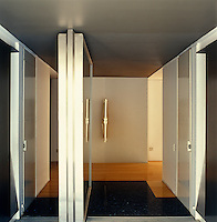 The pivoting steel entrance door to the Casa En El Aire open to reveal a marble and wood hallway