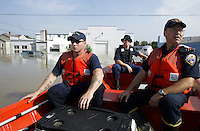 Members of the United States Coast Guard, Ian Ryan, left, and Joel Brown, center, and Findlay fireman Mark Sanders patrol the the flooded waters of the Blanchard River after heavy rains caused flooding Thursday, August 23, 2007, in Findlay, Ohio. The Blanchard River was close to 7 feet above flood stage at Findlay yesterday morning, the highest since a 1913 flood.
