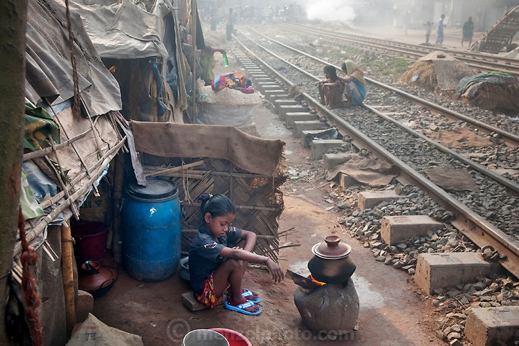 A girl sits by a fire in a slum settlement near the main train station in Dhaka, Bangladesh. (From the book What I Eat Around the World in 80 Diets.)