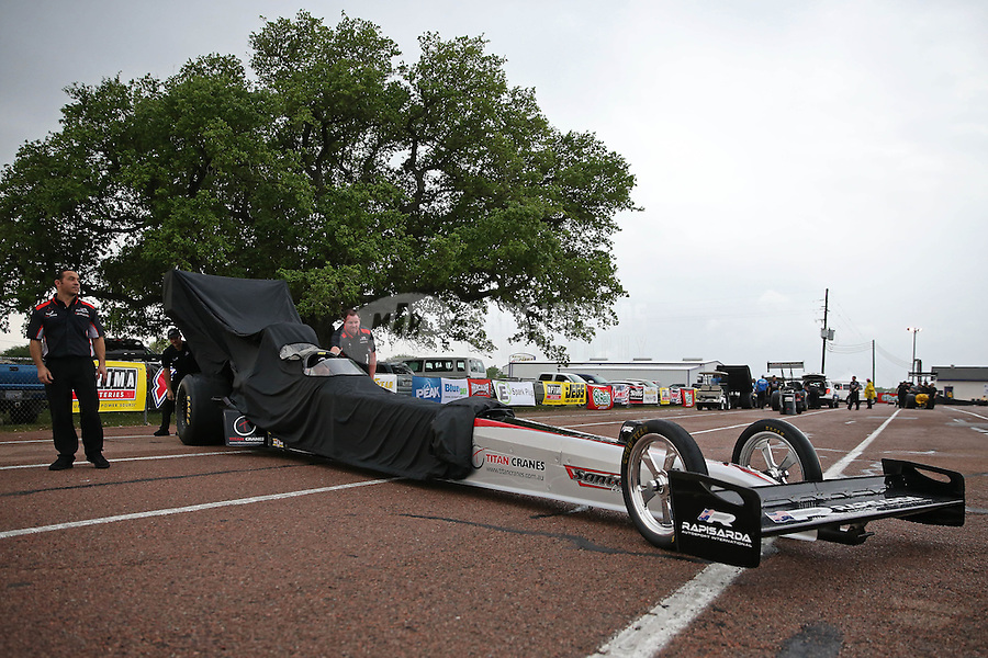 Apr. 27, 2013; Baytown, TX, USA: Crew members push the car of NHRA top fuel dragster driver Larry Dixon back to the pits during a rain delay to qualifying for the Spring Nationals at Royal Purple Raceway. Mandatory Credit: Mark J. Rebilas-