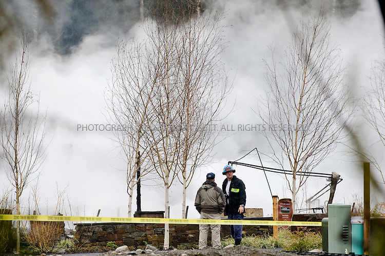 """3/3/2008 -- Woodinville,  Snohomish County, WA, USA.Smoke billows behind ATF investigators at the scene where three multi-million-dollar homes were destroyed by arson in an apparent act of domestic terrorism and that also damaged two others in the Maltby area of Snohomish County, east of Seattle, Wash. Near the burned homes, a spray-painted sign with the initials of the Earth Liberation Front was found. Local TV news showed the sign that read: """"Built Green? Nope black! McMansions in RCDs r not green. ELF"""".The homes were all unoccupied and were part of Seattle 'Street of Dreams' homes in the Quinn's Crossing development near Highway 522. The homes that burned were between 4,200 and 4,750 square feet in size, with prices up to nearly $2 million. The homes were built to be environmentally friendly an dused high-efficiency insulation and recycled materials...©2008 Stuart Isett. All rights reserved."""