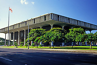 Diagonal shot of Hawaii State Capitol on Beretania Street in downtown Honolulu. Includes a clear view of the Hawaii State flag and grounds with flowering tropical trees.