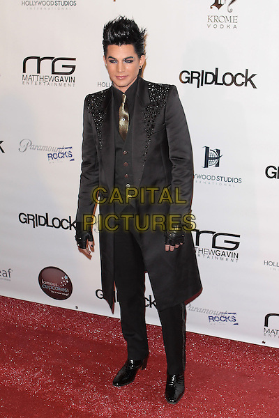 "ADAM LAMBERT.""Gridlock New Year's Eve Bash"" held at Paramount Studios, Hollywood, California, USA,  31st December 2009..full length black beaded shoulders suit coat gloves gold tie waistcoat fingerless gothic NYE high heels heeled shoes embellished .CAP/ADM/TC.©T. Conrad/AdMedia/Capital Pictures."