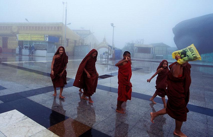 A line of young monks walk through the rain at Kyaiktiyo, Burma, July 2006. Photo: Ed Giles