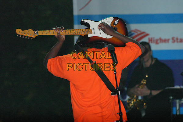 WYCLEF SEAN.Lights New UNICEF Crystal Snowflake at the Plaza Hotel in New York City..November 18, 2004.half length, stage, concert, playing guitar behind head, gesture, back, behind.www.capitalpictures.com.sales@capitalpictures.com.© Capital Pictures.