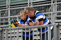 Two Bath supporters read the matchday programme prior to the game. Aviva Premiership match, between Bath Rugby and Leicester Tigers on September 20, 2014 at the Recreation Ground in Bath, England. Photo by: Patrick Khachfe / Onside Images