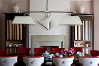 Comfortable red velvet tub chairs surround the dining room table which is lit by a double pendant light