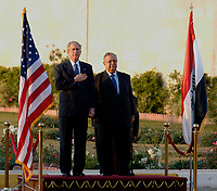 Baghdad, Iraq - December 14, 2008 -- United States President George W. Bush, left, and President Jalal Talabani of Iraq stand between the United States and Iraq flags, Sunday, December 14, 2008 during the playing of the U.S. national anthem. Bush is on his final visit to Iraq before the end of his second presidential term to meet with Iraqi leaders and sign a ceremonial copy of the security agreement. <br /> CAP/MPI/CNP/RS<br /> &copy;RS/CNP/MPI/Capital Pictures
