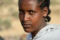 DJIBOUTI , Obock, from here ethiopian migrants try to cross bab el mandeb by boat to Yemen to go on to Saudi Arabia or Europe, ethiopian refugees from Tigray waiting outside the town for the smugglers, ethiopian orthodox christian with cross scar on the forehead / DSCHIBUTI, Obock, Meerenge Bab el Mandeb, mit Hilfe von Schleppern aethiopische Migranten versuchen hier nach Jemen ueberzusetzen, um weiter nach Saudi Arabien oder Europa zu gelangen, aethiopische Fluechtlinge aus Tigray warten ausserhalb der Stadt auf die Schmuggler, orthodoxe Christin mit auf der Stirn in die Haut eingeritztem Kreuz