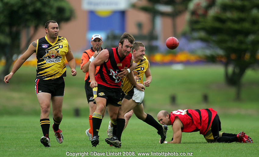 Andrew Hore punches a pass away in the tackle during the Preseason Cross-code Rugby Union v Australian Rules friendly between the Hurricanes and Wellington Tigers at  Elsdon Park, Porirua, New Zealand on Tuesday, 15 January 2008. Photo: Dave Lintott / lintottphoto.co.nz