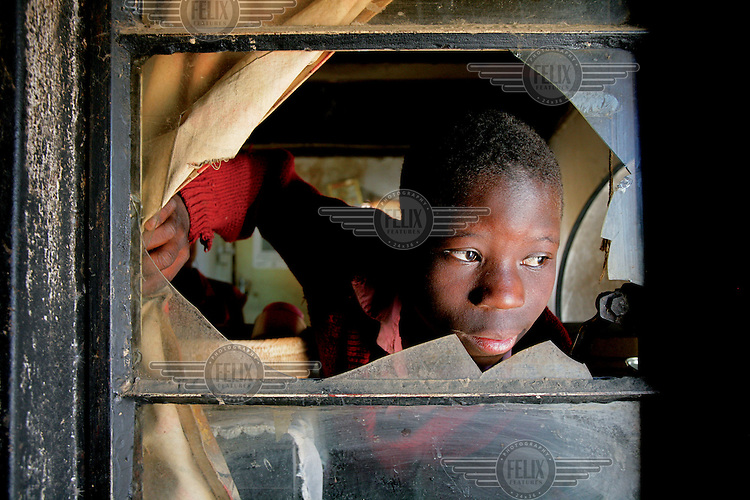 A boy orphaned by AIDS in his home in Harare..