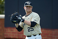 Wake Forest Demon Deacons bullpen catcher Chris Shafer (25) warms up the starting pitcher prior to the game against the Liberty Flames at David F. Couch Ballpark on April 25, 2018 in  Winston-Salem, North Carolina.  The Demon Deacons defeated the Flames 8-7.  (Brian Westerholt/Four Seam Images)