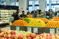Workers arrange oranges in the produce department in the new Whole Foods Market in Newark, NJ on opening day Wednesday, March 1, 2017. The store is the chain's 17th store to open in New Jersey. The 29,000 square foot store located in the redeveloped former Hahne & Co. department store building is seen as a harbinger of the revitalization of Newark which never fully recovered from the riots in the 1960's.  (© Richard B. Levine)