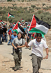 """Villagers, Israeli and foreign peace activists wave the Palestinian flag as they make their way towards the separation barrier being built by Israeli near their village and which the Israeli Supreme Court ordered that part of it be rerouted the occupied West Bank village of Bilin 12 kilometres (about seven miles) west of the Palestinian city of Ramallah.the Israeli Supreme Court's ruling that a section of its controversial separation barrier there must be rerouted sighting that the route of the separation barrier in the Bilin area was """"highly prejudicial"""" to the villagers and demanded that the government map out an alternative route """"within a reasonable period."""""""