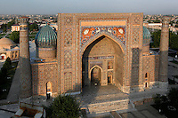 "Aerial view of the Sher-Dor Madrasah, 1619-36, Samarkand, Uzbekistan, pictured on July 15, 2010 at sunset which lights up the elaborately tiled facade and domes. The Sher-Dor Madrasah, commissioned by Yalangtush Bakhodur as part of the Registan ensemble, and designed by Abdujabor, takes its name, ""Having Tigers"", from the double mosaic (restored in the 20th century) on the tympans of the portal arch showing suns and tigers attacking deer. Samarkand, a city on the Silk Road, founded as Afrosiab in the 7th century BC, is a meeting point for the world's cultures. Its most important development was in the Timurid period, 14th to 15th centuries. Picture by Manuel Cohen."
