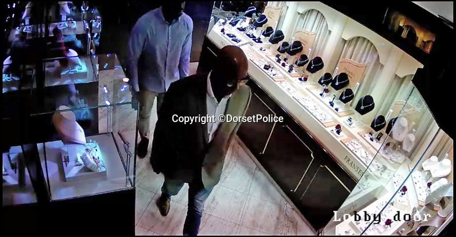 BNPS.co.uk (01202) 558833Pic: DorsetPolice/BNPS<br /> <br /> Screenshots from shocking CCTV footage of an armed robbery at a jewellers in Bournemouth.<br /> <br /> Mustafa Ali and Michael Adiat can be seen entering Franses Jewellers in Bournemouth.<br /> <br /> Shocking CCTV that shows how two violent armed robbers posed as respectable customers before overpowering staff at a jewellers armed with handguns and a lump hammer has emerged.The two smart looking men sat down at a desk with shop assistant Ben-Simon Charles, who showed them luxury watches worth up to £50,000.Without warning one of them stands up, pulls out a pistol hidden under his jacket. His accomplice pulls a gun from his waistband and grabs Mr  Charles in a headlock while threatening to kill him and shop owner Jeff Franses.The assailant wielding the hammer threatens a third employee with it before smashing the reinforced glass of display cabinets to get to the expensive watches.