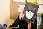 Education Middle School grade 8 art activity cut paper self portraits girl holding up art work to cover her face horizontal
