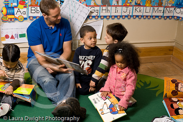 Education preschoool children ages 3-5 male teacher sitting with group of children reading book to them as other children sit nearby looking at their own books horizontal