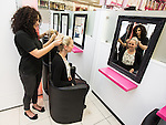 © Joel Goodman - 07973 332324 . 15 August 2013 . Paul's Hair World , Arndale Centre, Manchester , UK . Shop manager Nikki Purcell (31 , from Cheshire) has her hair done by Josie Humphries (17) (both correct) in the new booths . Newly reopened retail outlet for Pauls Hair World . The original outlet on Oldham Street was destroyed in a fire on 13th July 2013 . The fire claimed the life of firefighter Stephen Hunt . Photo credit : Joel Goodman
