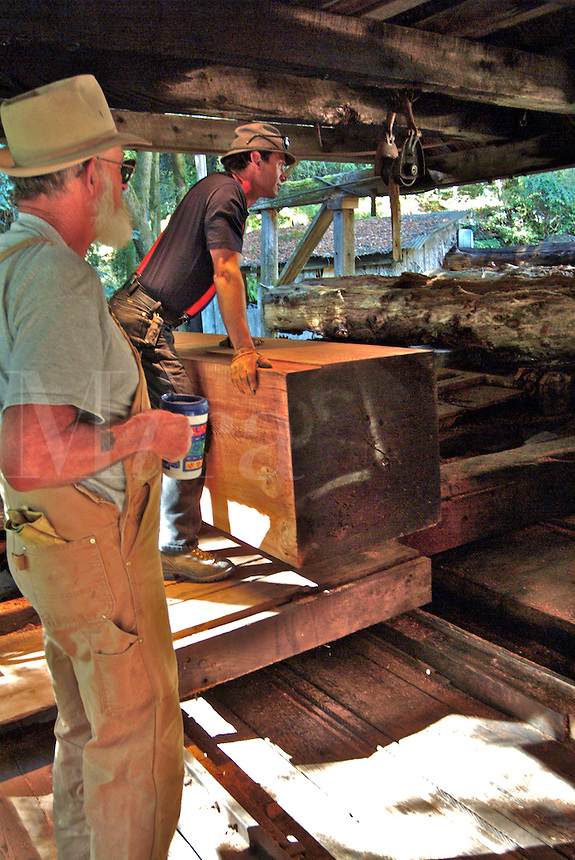 Two saw mill workers are preparing to cut a large redwood log that has already been trimmed and squared on all four sides in an old saw mill in Occidental California