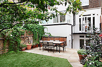 A table and chairs set on a paved terrace in the rear garden of a London town house.
