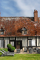The traditional half-timbered exterior of a medieval manor house in Normandy