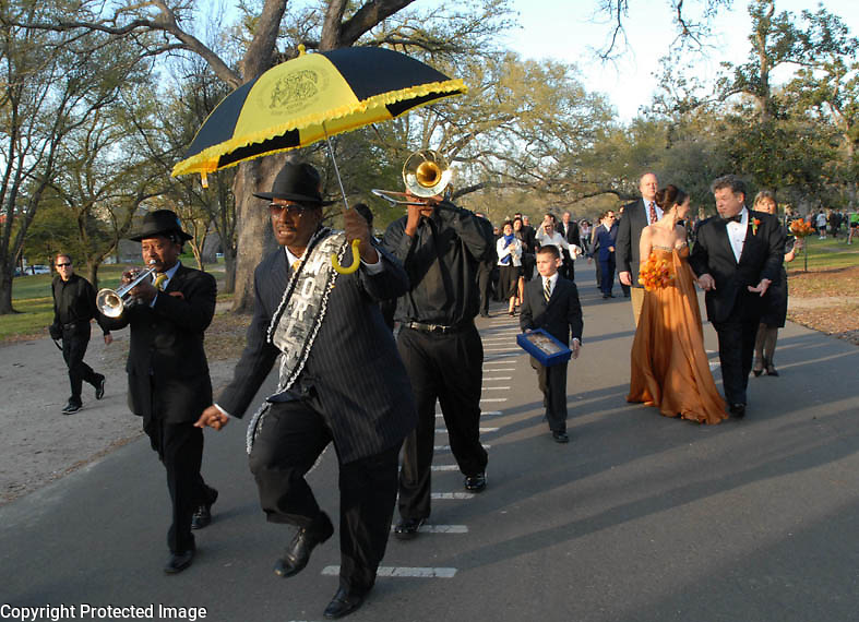 Guests at the Fertel wedding are escorted by a second-line to the reception under the giant live oaks in Audubon Park, New Orleans, Saturday, March 10, 2007..(Cheryl Gerber for New York Times).. Weddings, New Orleans Photographer