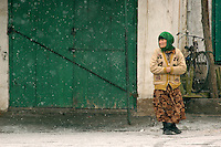 A Uyghur woman takes a chilly walks across the main square of a neighborhood on the outskirts of Kashgar. The oasis city on the far northwest border of China was a fabled crossroad on the ancient Silk Road and remains an important center of trade for the Xinjiang Uyghur Autonomous Region..