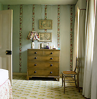 A further set of John Fowler's gothic pelmets is in evidence in the bedroom where a simple chest of drawers stands against a grey-painted wall with bands of vertical flowers creating a striped effect