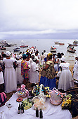Salvador, Bahia, Brazil. Candomble followers with offerings spread out on a white sheet; Festival of Iemanja.