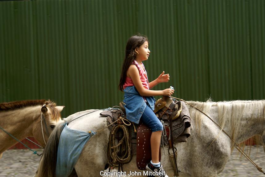 Girl on horseback, Antigua, Guatemala. Antigua is a UNESCO World heritage site...