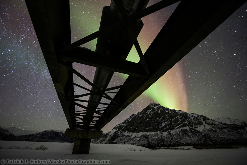 Northern Lights and the Alaska oil pipeline crosses the Dietrich river, Mount Dillon of the Brooks Range in the distance.