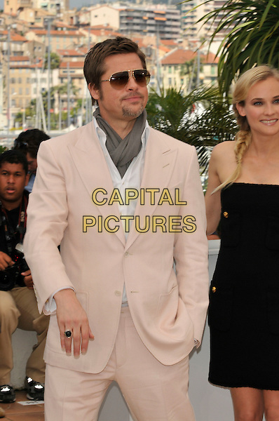 """BRAD PITT & DIANE KRUGER.Photocall for """"Inglourious Basterds"""" at the Palais des Festivals during the 62nd Annual Cannes Film Festival, Cannes, France..May 20th, 2009.half length facial goatee hair black strapless dress beige suit scarf sunglasses shades hand in pocket ring grey gray.CAP/PL.©Phil Loftus/Capital Pictures."""