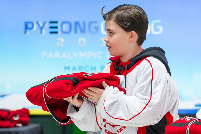 TORONTO, ON - FEBRUARY 11: A player from the Elmvale Bears sledge hockey team holds the Team Canada jackets on stage as Hockey Canada reveals the players and coaching staff who will represent Team Canada in Men's Sledge Hockey at the upcoming Paralympic 2018 Winter Games in PyeongChang, South Korea on February 11, 2018 in the Atrium at the Canadian Broadcasting Corporation building in Toronto, Canada. (Photo by Adam Pulicicchio/Hockey Canada)