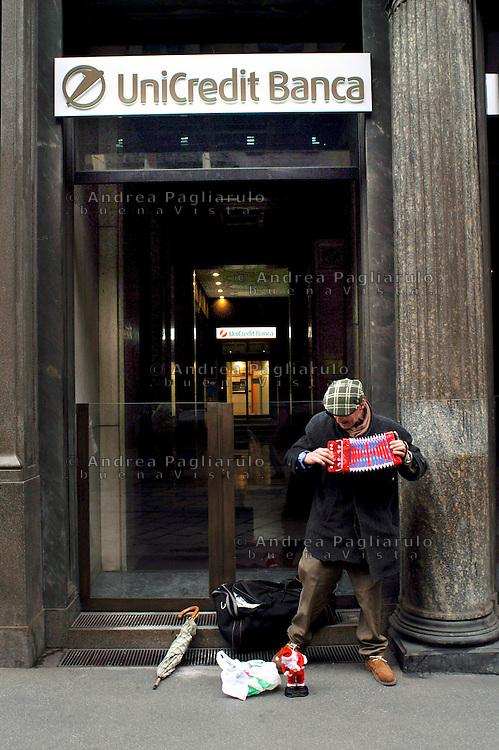 Milano, suonatore ambulante davanti la Banca Unicredit di via Manzoni.<br /> Milan, street musician in front of Unicredit Bank.