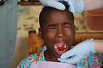 TANGA, TANZANIA - JULY 7:   A young girl screams in pain after having her teeth removed by a Non-Governmental Organization that deals with treatment and medicine on July 7, 2010 in Tanga, Tanzania. The Tanzanian health care system has seen a gradual decline with low medical staff morale due to declining wages and operational difficulties in the central medical stores and domestic pharmaceuticals industries.