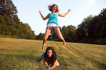 Two early twenties caucasian females play leap frog on a clear afternoon in a Connecticut, USA, meadow.