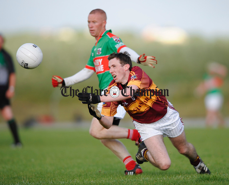 12 Miltown's Michael Hehir gets the ball away as Michael Hogan of Kilmurry Ibrickane moves in during their Cusack Cup sem-final at Kilmihil. Photograph by John Kelly.