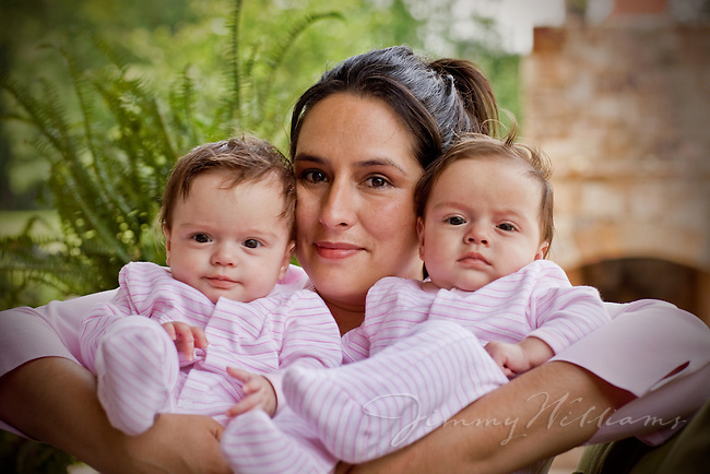 A close up shot of a mother holding her twin babies in her arms.